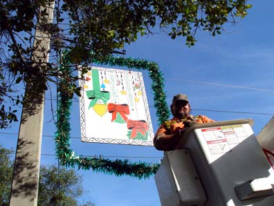 A city forestry worker hanging a Christmas card on Morse Boulevard in december 2002.
